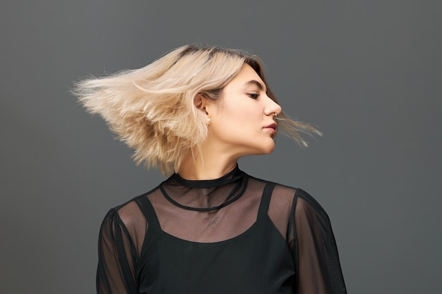 People, lifestyle, fun, festivity and party concept. isolated shot of good looking charming young female with bob blonde hairstyle enjoying nice music, dancing with eyes closed, hair flowing in wind