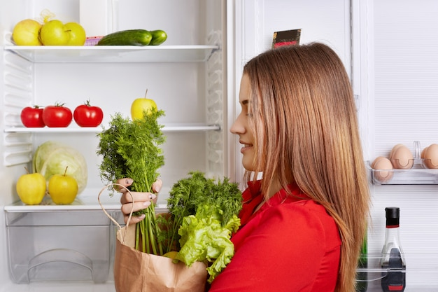 People, lifestyle and healthy eating concept. sideways shot of adorable woman holds paper box with dill and lettuce, has fridge full of fruits and vegetables, going to make vegeterian fresh salad