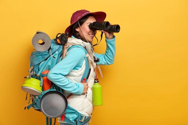 Люди, образ жизни, праздник, концепция туризма. веселая туристка наблюдает что-то в бинокль, стоит с рюкзаком, носит повседневную спортивную одежду.