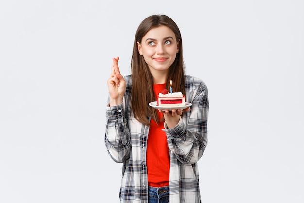 人々のライフスタイル、休日やお祝い、感情の概念。カジュアルな服を着て、指を交差させ、願い事をして、b-dayケーキを持って、ろうそくを吹いて見上げる夢のような希望に満ちた誕生日の女の子。