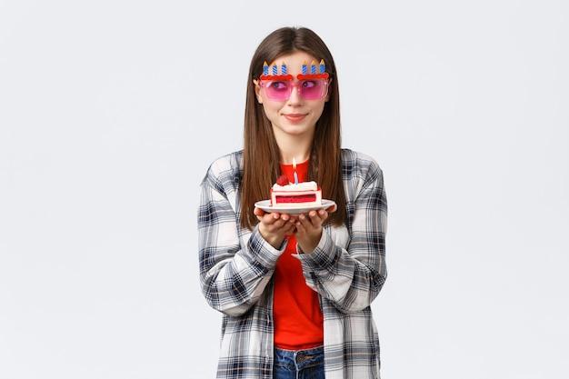 Stile di vita delle persone, vacanze e celebrazioni, concetto di emozioni. ragazza di compleanno carina e sciocca con occhiali divertenti, distogliere lo sguardo, pensa al desiderio come se soffiasse una candela accesa sulla torta di b-day, sorridendo eccitata.