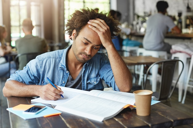 People, lifestyle, learning, knowledge and education concept. portrait of attractive focused african american student busy working on course paper, taking down notes from textbook in copybook