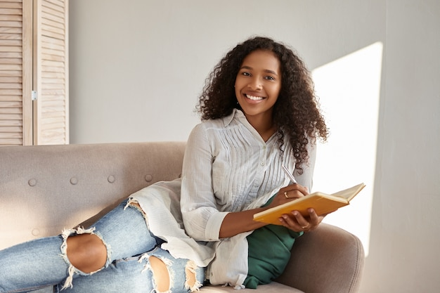 People, lifestyle, leisure, hobby and rest. adorable charming young dark skinned woman with afro hairdo relaxing on comfortable gray couch smiling, writing down goals and plans in diary