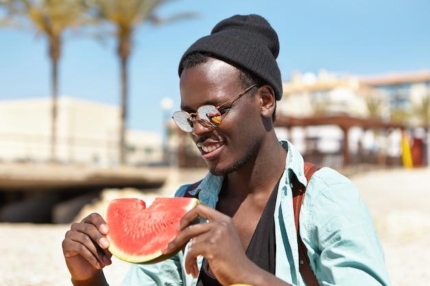 人、ライフスタイル、レジャー、休暇、旅行の概念。日当たりの良い夏の日に甘くて熟したフルーツを楽しんで、彼の手でジューシーなスイカのスライスを保持している幸せなリラックスしたアフロアメリカ人男性の観光客