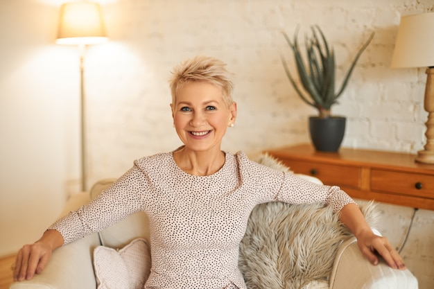 People, lifestyle and mature age concept. horizontal image of good looking confident female with short dyed hair relaxing at home, sitting comfortably in armchair, smiling broadly