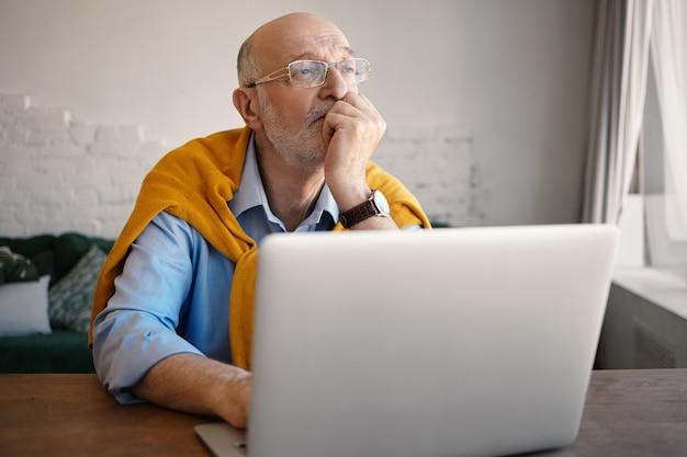 사람, 라이프 스타일, 현대 기술, 나이, 비즈니스, 직업 및 직업 개념. 꿈꾸는 얼굴을 가진 랩톱을 사용하여 그의 블로그에 기사를 입력하는 잘 생긴 백인 수염 난 남자 작가의 실내 샷