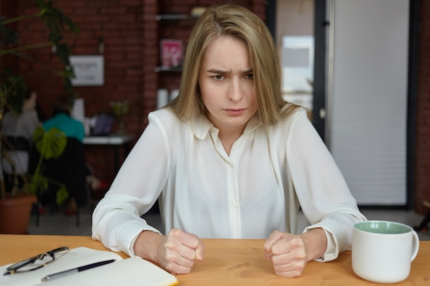 People, lifestyle and negative human emotions. furious young businesswoman in white blouse working while sitting at cafeteria during coffee break, being angry because her lunch is not ready yet