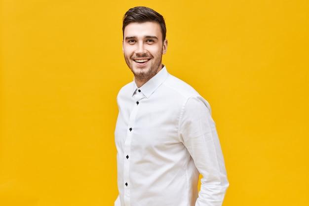 사람, 라이프 스타일, 성공 및 자신감 개념. 자신감이 넓은 미소로 고립 된 포즈 공식적인 세련된 옷을 입고 쾌활한 매력적인 젊은 백인 남성