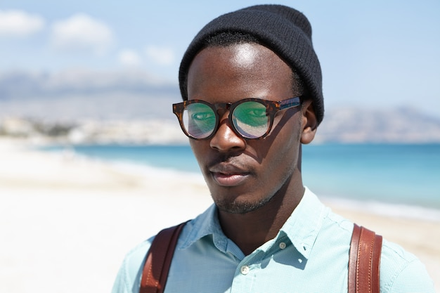 Persone, stile di vita, estate e viaggi. ritratto all'aperto dei pantaloni a vita bassa attraenti che si rilassano sulla spiaggia da solo, godendo del tempo soleggiato caldo