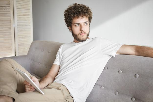 人、ライフスタイル、テクノロジー、コミュニケーションのコンセプト。無料のwifiを使用して、自宅でタッチパッドpcに取り組んで、物思いにふける外観を持つファジーなひげと巻き毛を持つ魅力的な若い男性ブロガー