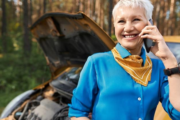 人、ライフスタイル、交通機関、そして現代のテクノロジーのコンセプト。開いたフードで壊れた車のそばに立って、道端での援助を呼び、助けを求めて、笑顔で美しい金髪の引退した女性