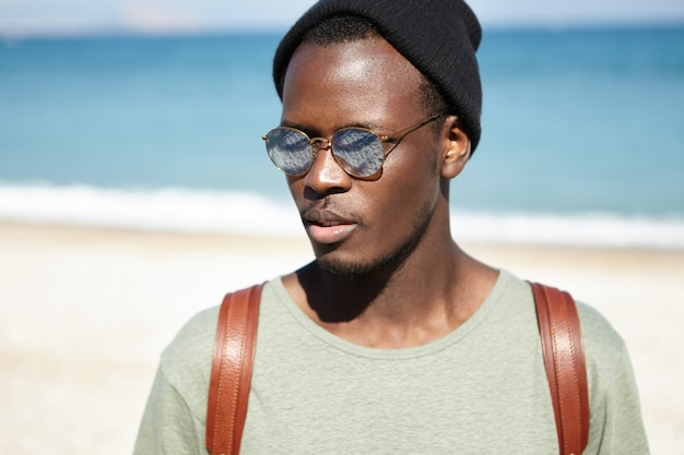 People, lifestyle, travel and adventure concept. close up shot of attractive young african american tourist with backpack, having nice walk along seashore