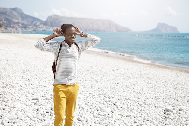 People and lifestyle. travel and tourism. handsome cheerful young afro american mantraveler wearing stylish clothing and accessories standing on pebble beach, admiring beautiful marine view