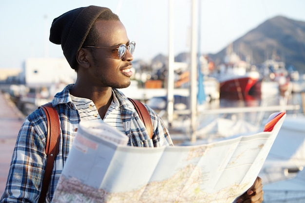 People, lifestyle, traveling and adventures concept. man on quay surrounded by yachts and ships in fashionable hat and mirror sunglasses holding paper guide looking aside at sea with pleased smile