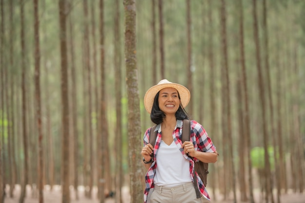 People and lifestyles adventure, travel, tourism, hike and people concept - traveller women walking in the forest of smiling  walking with backpack, hat in woods.