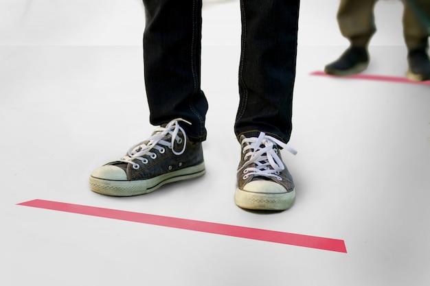 Люди выстраиваются в линию и стоят на красном знаке на полу, чтобы держаться на расстоянии от других