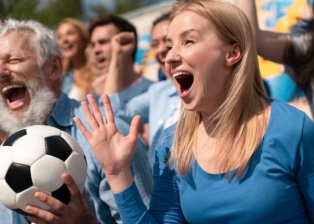 화창한 날에 축구 경기를 보는 사람들