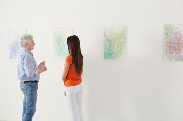 Люди смотрят картину в художественной галерее