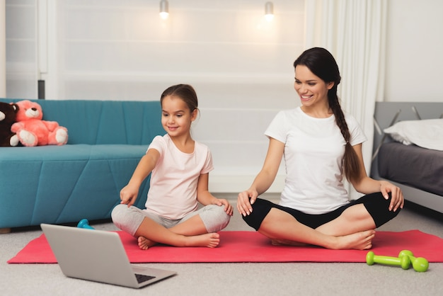 People in lotus position at home look at a laptop