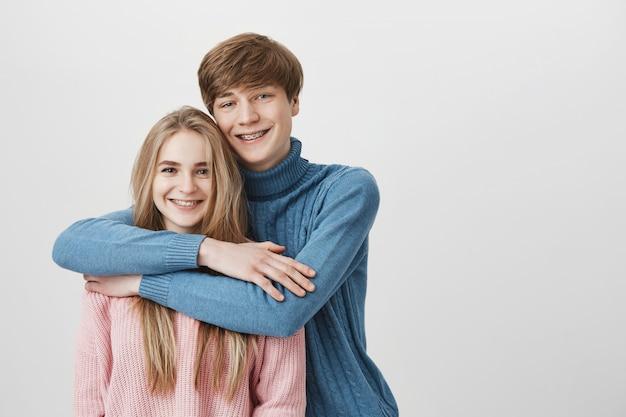 Люди, любовь и отношения концепция. сладкий выстрел из счастливой улыбающейся пары, одетой небрежно обнимающейся