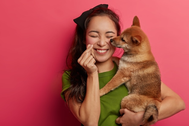 People, love to animals concept. positive korean girl plays with shiba inu dog, makes mini heart hand gesture