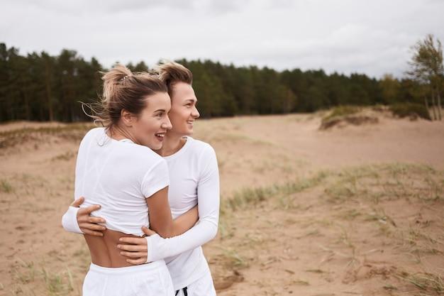 사람, 사랑, 가족, 관계 및 행복 개념. 야외에서 흰색 옷을 입고 편안한 행복 한 커플의 그림. 야외에서 시간을 보내는 그녀의 귀여운 십 대 아들을 껴 안은 즐거운 금발 어머니