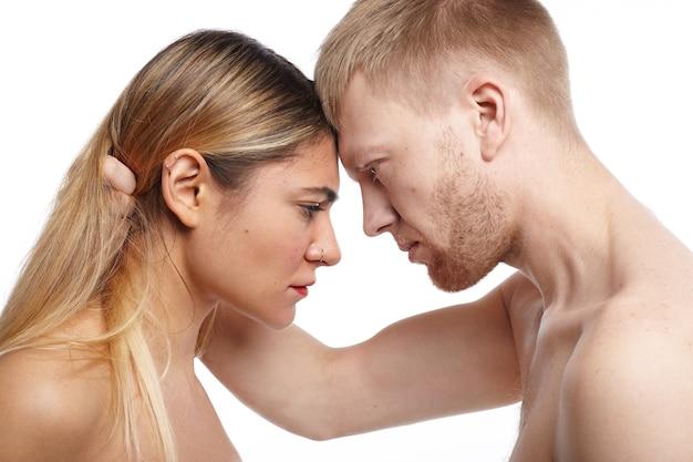 人、愛、親密さ、セックス、関係の概念。彼の魅力的なトップレスのガールフレンドの髪をつかみ、情熱を持って彼女を見つめている情熱的な上半身裸のヨーロッパのひげを生やした男の横向きのショット