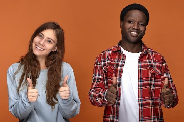 Persone, amore, gioia, felicità e concetto di relazioni interrazziali. due migliori amici di diverse etnie che fanno segni di pollice in alto e sorridono, felici di vedersi dopo una lunga separazione
