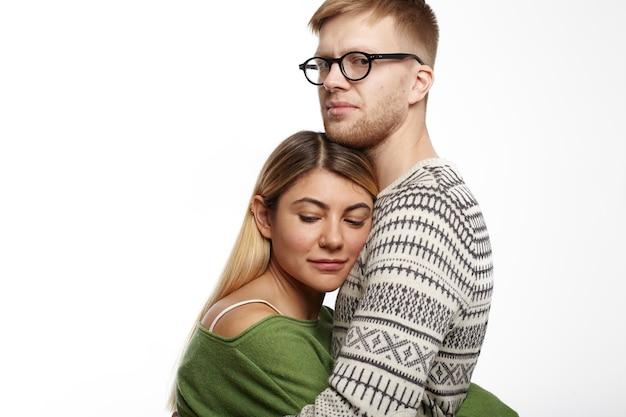 人、愛、恋愛、人間関係の概念。彼女を手放したくない、彼の魅力的なガールフレンドをしっかりと抱き締めるセーターと眼鏡のハンサムな若い白人のひげを生やした男