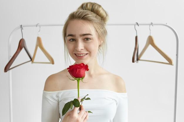 Persone, amore, romanticismo, bellezza e concetto di affetto. attraente giovane donna caucasica che indossa la parte superiore bianca aperta delle spalle, sorridente, con in mano una rosa rossa dal suo sconosciuto ammiratore segreto