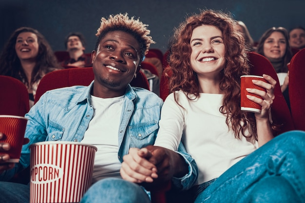 People in love watching movie in movie theater.