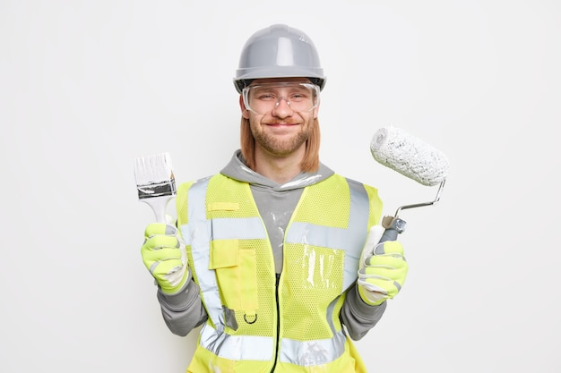 People maintenance and occupation concept. positive busy professional male builder dressed in construction clothes holds brush and paint roller wears protective hardhat transparent glasses uniform