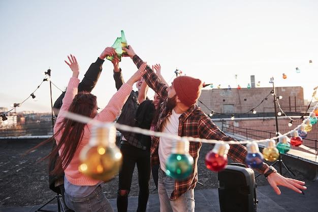 人々は乾杯をします。屋上の休日。陽気な友人グループがアルコールで手を挙げた