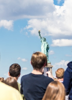 People make photo of the statue of liberty, new york city, ny, usa