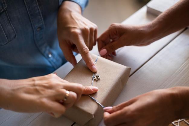 Люди делают бумажный подарок счастливой хануки