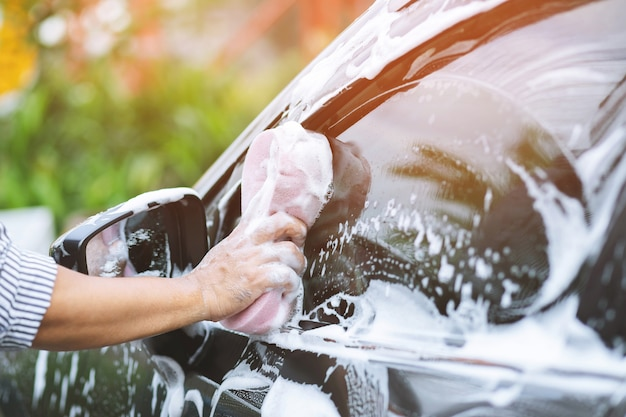 People man holding hand pink sponge for washing car. cleaning wheel tire. concept car wash clean.