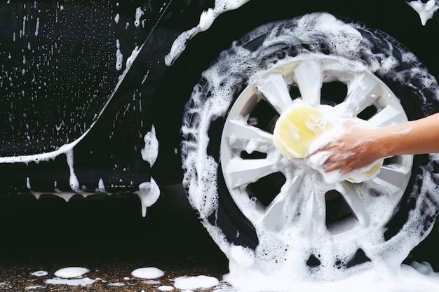 車を洗うために黄色いスポンジを手に持っている人。ホイールタイヤのクリーニング。コンセプトカーウォッシュクリーン。