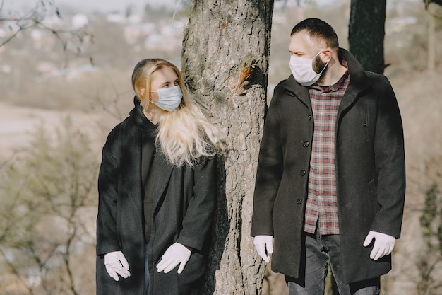 People in masks walks in a forest