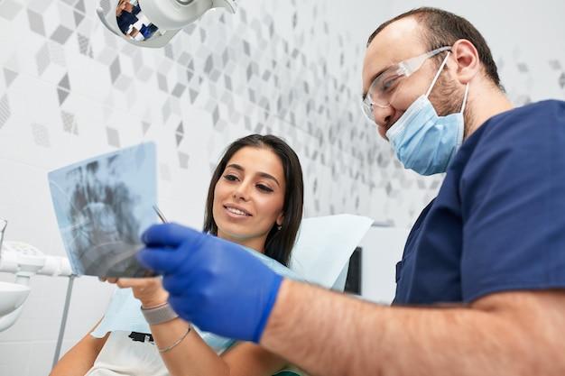 사람, 의학, 구강 및 건강 관리 개념 - 치과 진료소에서 여성 환자에게 작업 계획을 보여주는 행복한 남성 치과의사.