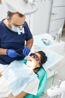 Люди, медицина, стоматология и концепция здравоохранения - счастливый мужской стоматолог с женщиной-пациентом в офисе стоматологической клиники.