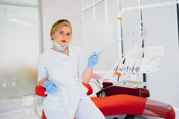 People, medicine, stomatology and healthcare concept - happy young female dentist with tools over medical office background
