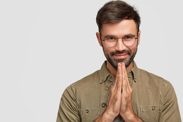 People and meditation concept. faithful pleased young european man with beard and mustache, keeps palms together, believes in something good, dressed in fashionable shirt, poses indoor alone