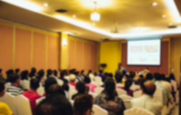 People in meeting or conference room blurred for background.