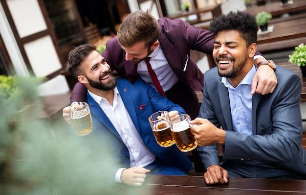 Люди, мужчины, досуг, дружба и концепция праздника. счастливые деловые друзья-мужчины пьют пиво и чокаются в баре или пабе
