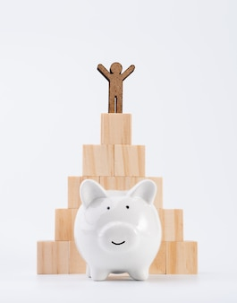 People model stand on wood cubes pyramid and piggy bank isolated