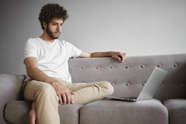 人、モデム技術、教育の概念。白いtシャツを着て、ラップトップコンピューターを使用し、表情を集中させ、ウェビナーをオンラインで視聴している、焦点を絞った若い無精ひげを生やした男性の率直なショット