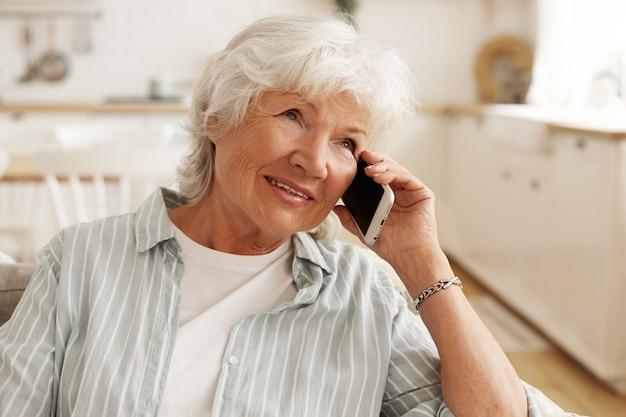 人、現代の電子機器、テクノロジー、コミュニケーション。素敵な電話の会話を楽しんで、ソファに座って、彼女の耳に携帯電話を持って、笑顔の短い白髪の年配の年配の女性
