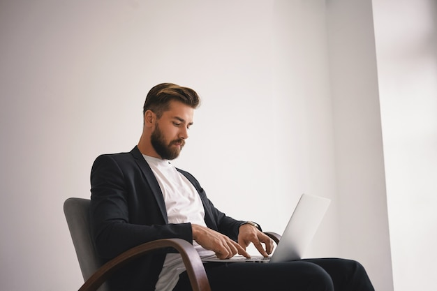 Люди, современный образ жизни, бизнес и концепция гаджетов. изолированный снимок красивого молодого бизнесмена с подстриженной бородой и стильной прической, использующего универсальный ноутбук, общаясь с партнерами в интернете