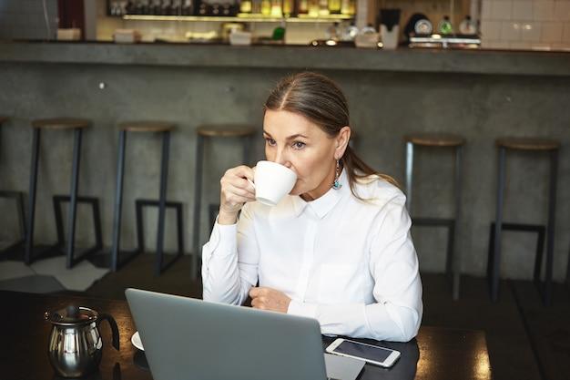 사람, 현대적인 라이프 스타일, 기술, 커뮤니케이션 및 레저 개념. 혼자 카페테리아에서 커피를 마시면서 원격 작업을 위해 랩톱 pc를 사용하는 회색 머리를 가진 심각한 사려 깊은 은퇴 한 아가씨