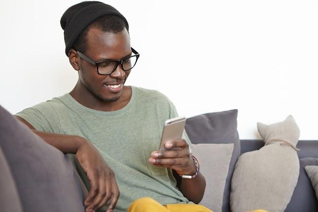 人、現代のライフスタイル、技術、コミュニケーションの概念。陽気な若い浅黒い学生読書メッセージ